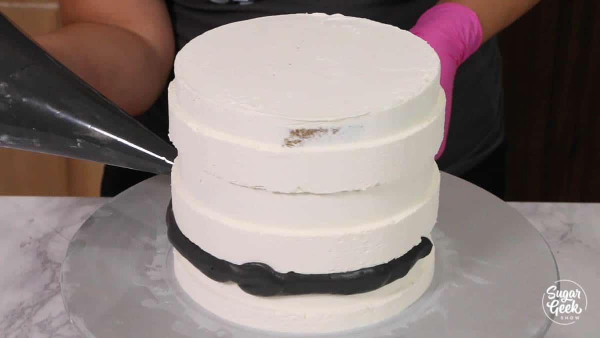 aggiungere strisce di crema al burro nera alla torta di crema al burro bianca con una sac à poche