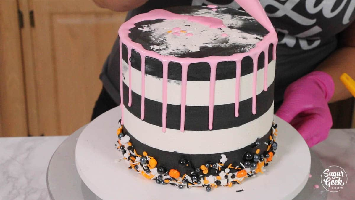 pink drip being added to black and white buttercream cake with halloween sprinkles