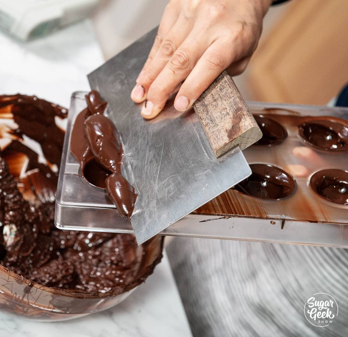 scraping excess chocolate off the mold with a bench scraper