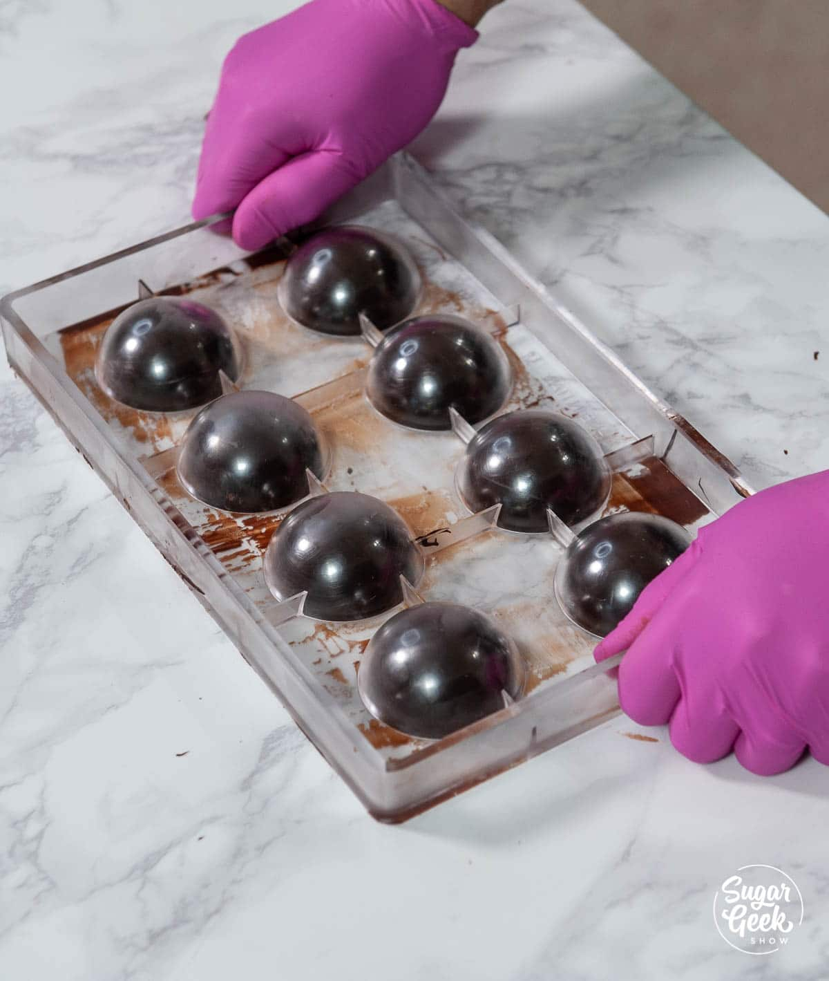 sphere mold with chocolate on a white counter