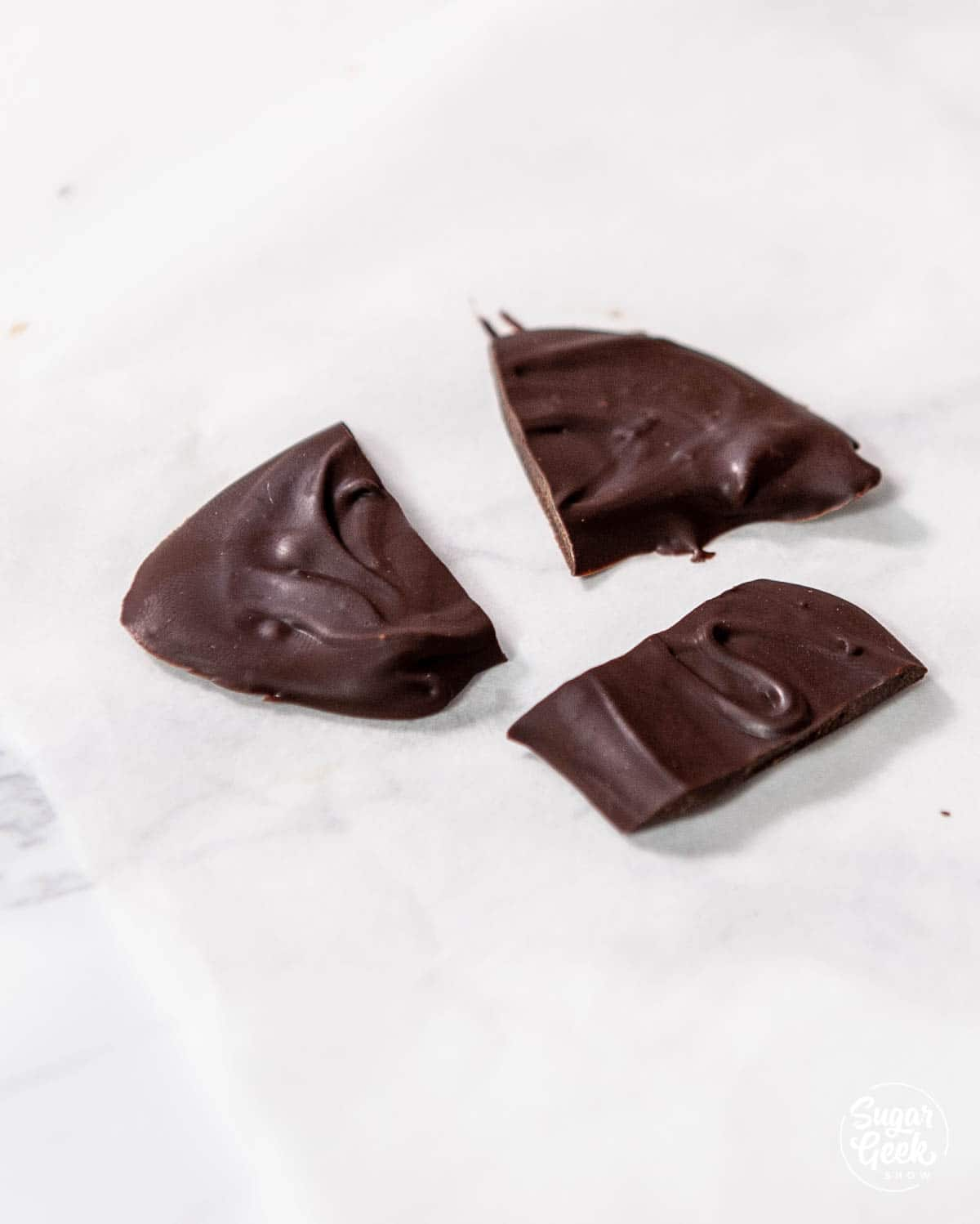 three broken pieces of chocolate