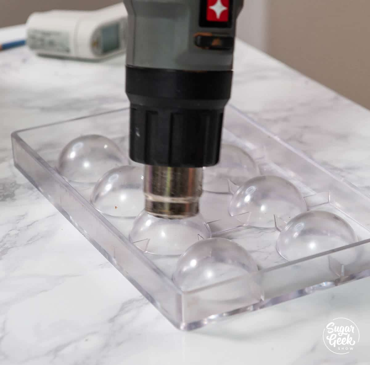 warming an acrylic sphere mold with a heat gun