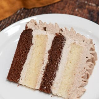 chocolate and vanilla cake slice with chocolate whipped cream on a white plate