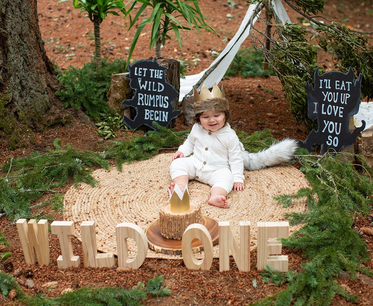 one year old boy with cake and wooden letters in the foreground