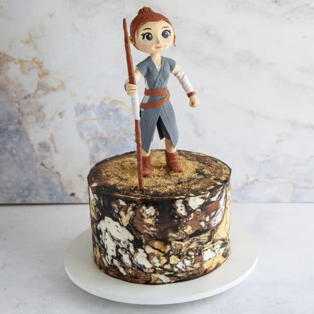 Marble buttercream cake tier with cute standing cake topper holding a staff