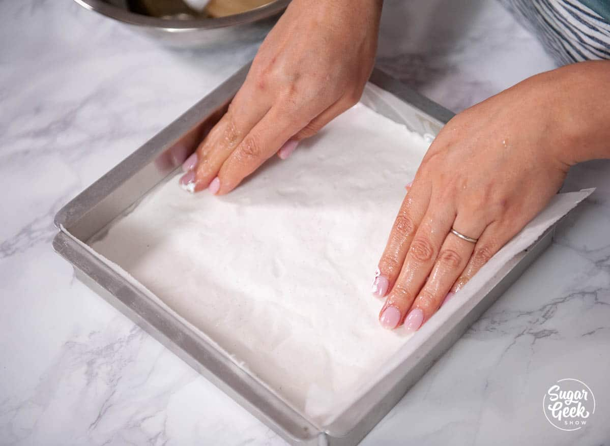 marshmallow fluff going into a greased square pan