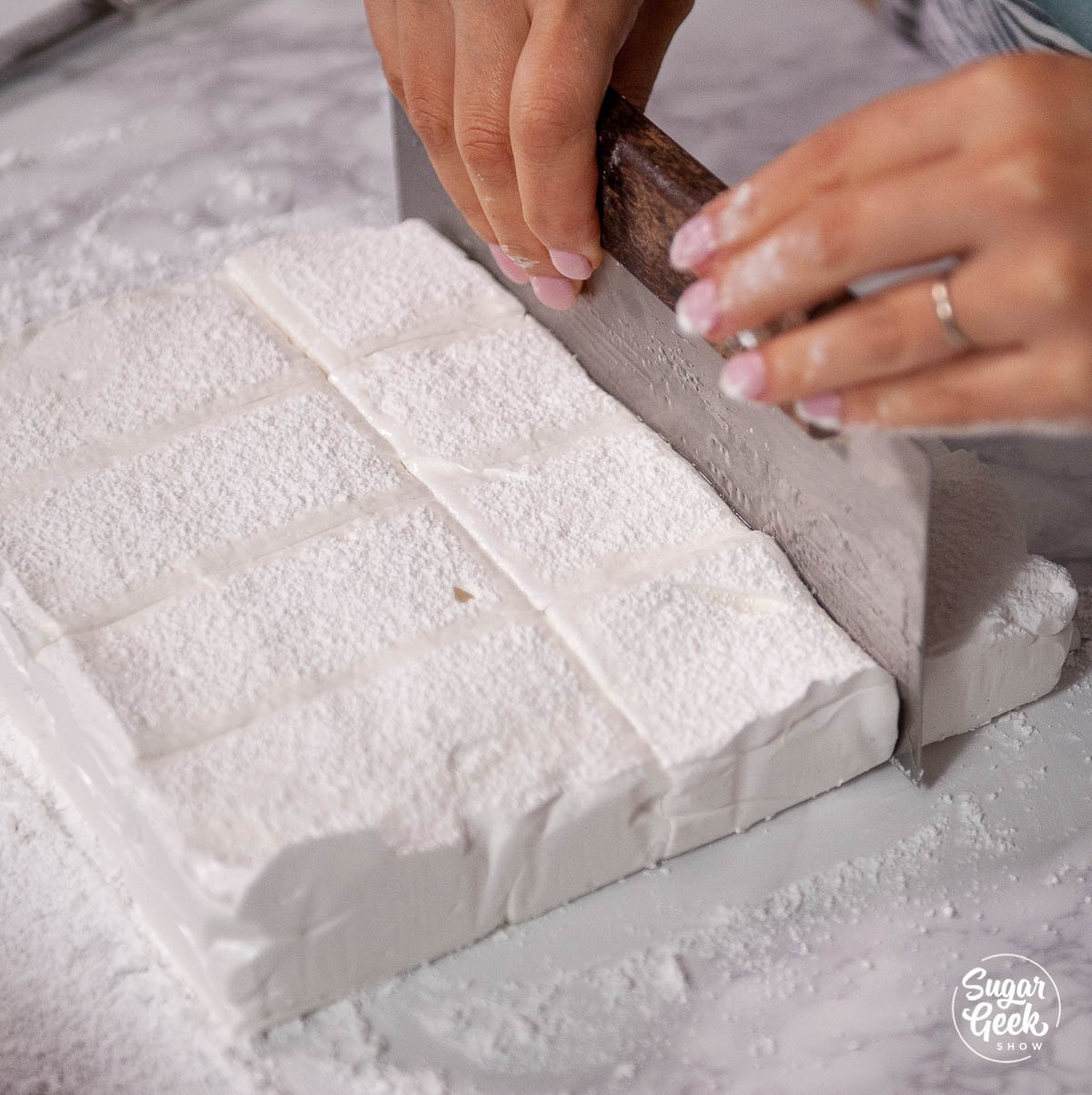 cut homemade marshmallows with an oiled bench scraper