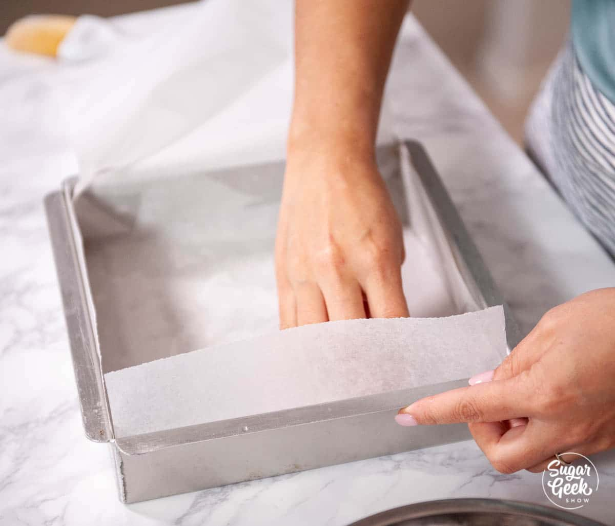 lining a square metal pan with parchment paper