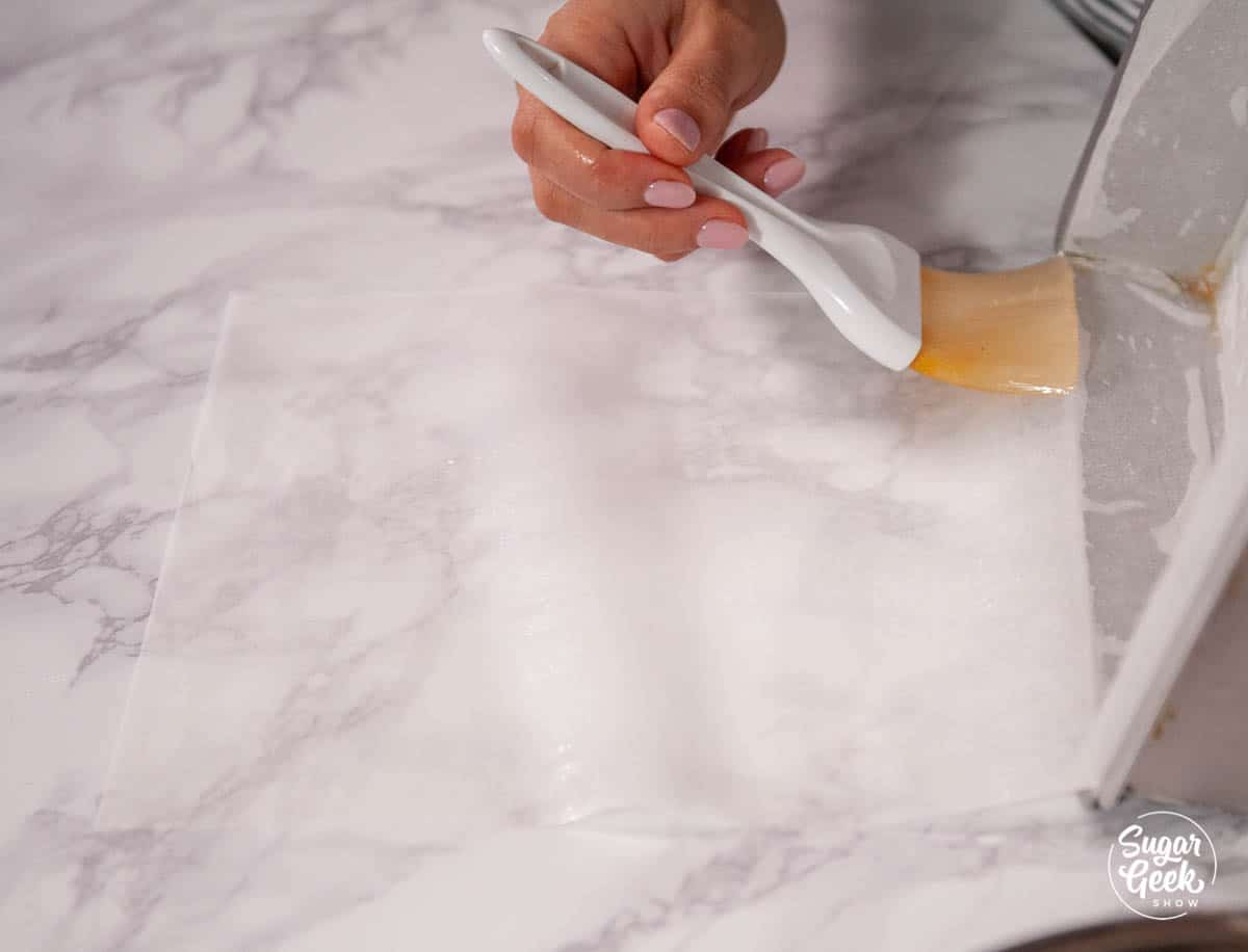 hand brushing oil onto parchment paper with a pastry brush
