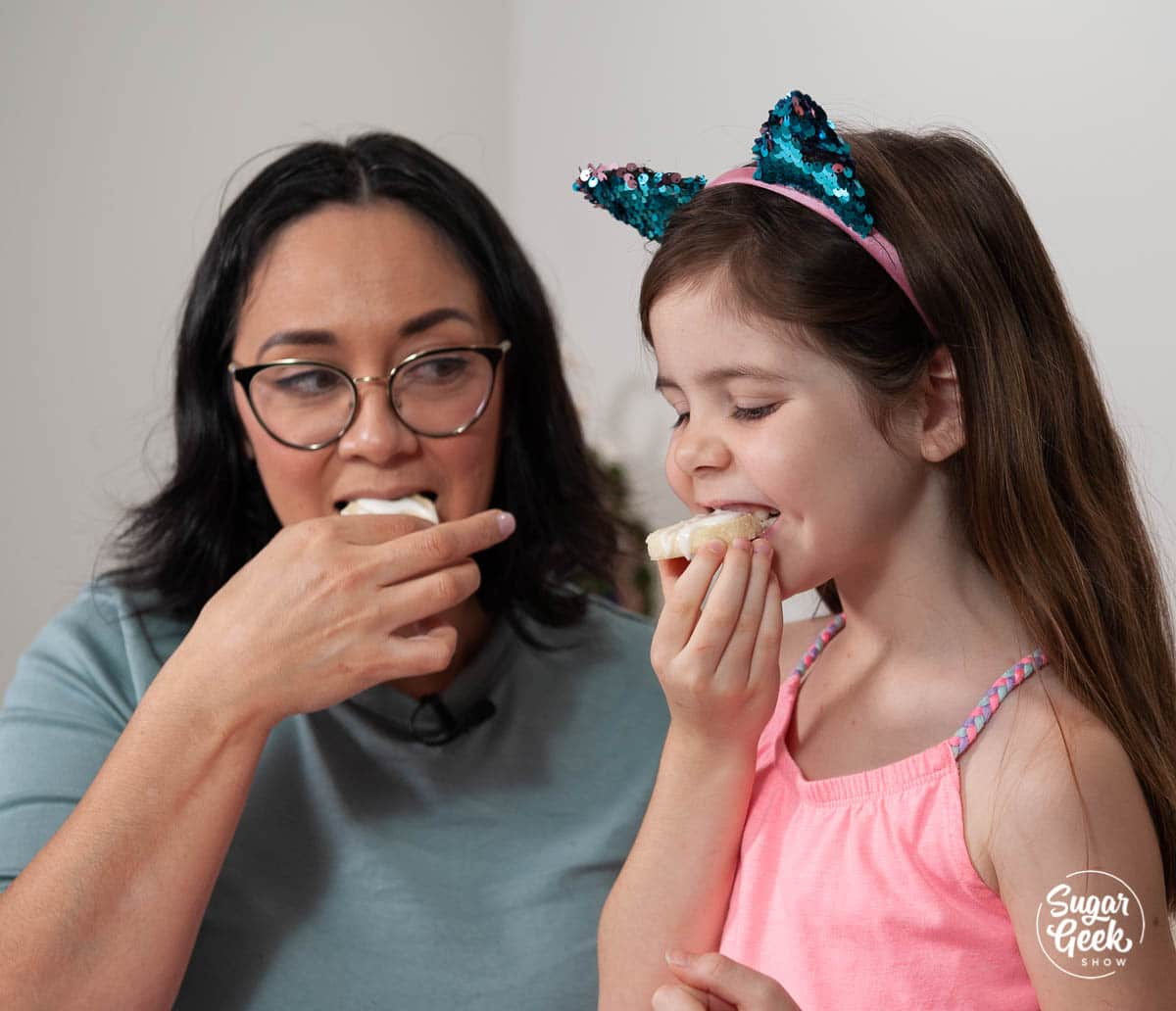 woman and girl biting into lemon shortbread cookies