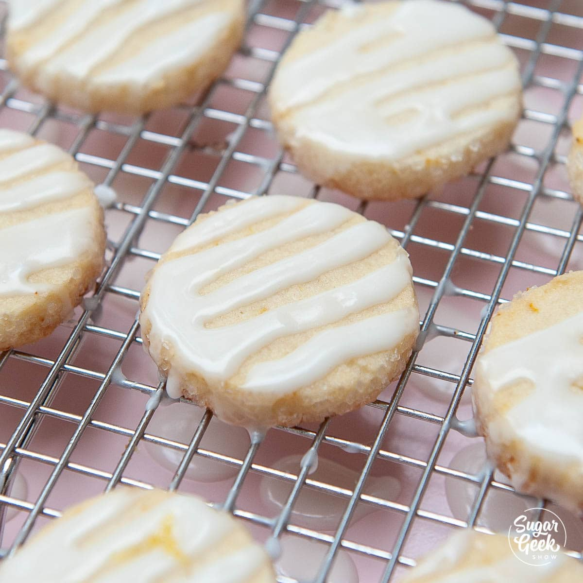 closeup of lemon shortbread cookies with lemon glaze on a cooling rack