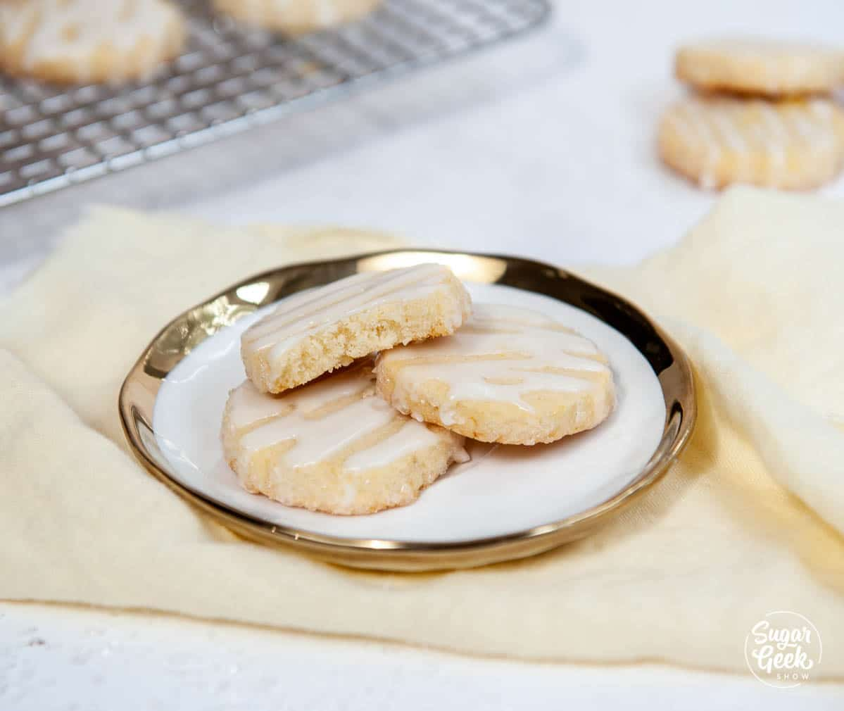 lemon shortbread cookies on a white plate with gold edge on a yellow napkin