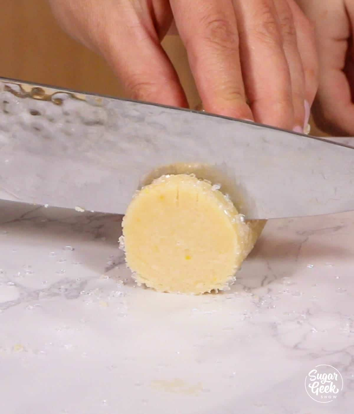 slicing lemon shortbread cookie dough with a knife