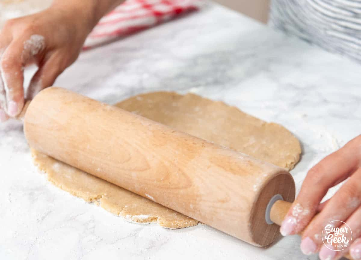 rolling Linzer cookie dough out with a wooden rolling pin