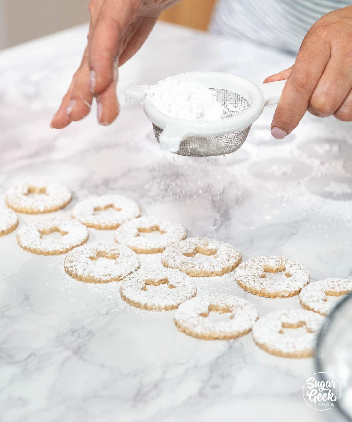 dusting linzer cookies with powdered sugar