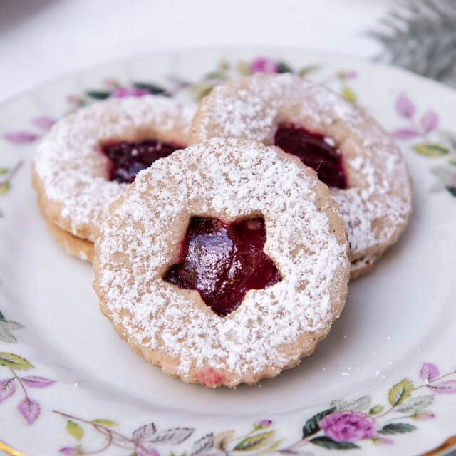 close up of linzer cookies on a floral plate
