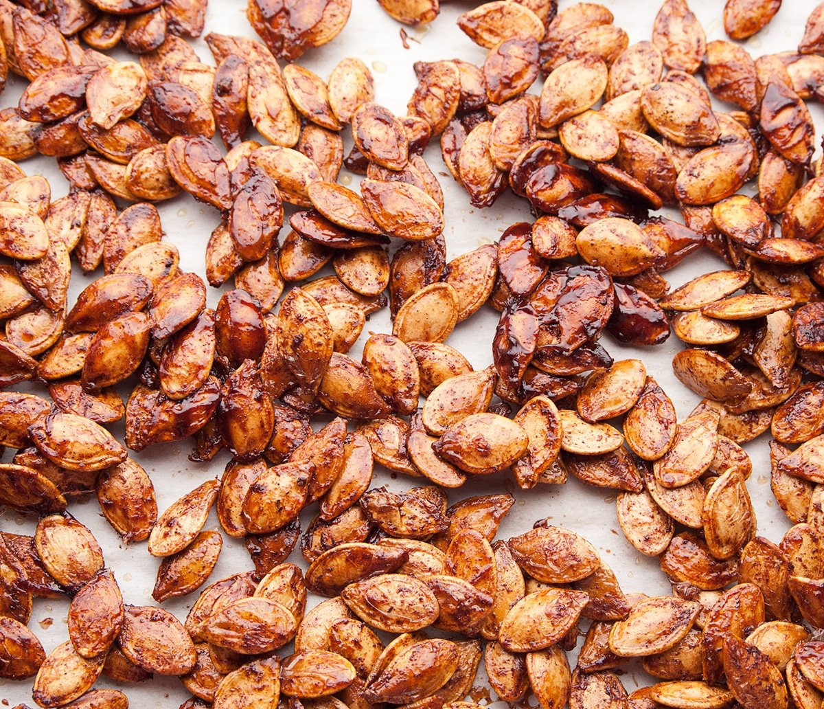 A parchment lined baking sheet is covered with roasted pumpkin seeds that were coated in maple syrup and spices- a delicious way to use up the leftover seeds from pumpkin carving. High point of view- looking down.