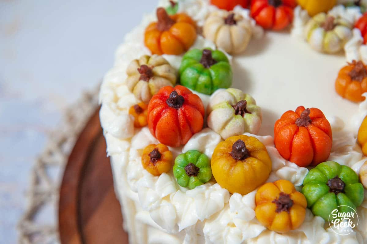 closeup of marzipan candy pumpkins on a cake