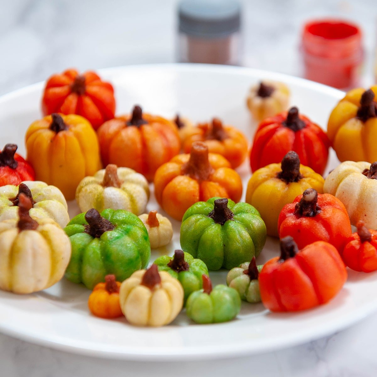 close up of marzipan candy pumpkins on a white plate
