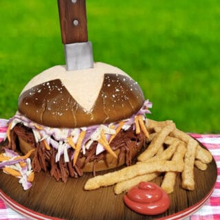 cake sculpted to look like a pulled pork sandwich with french fries, ketchup and a pretzel bun