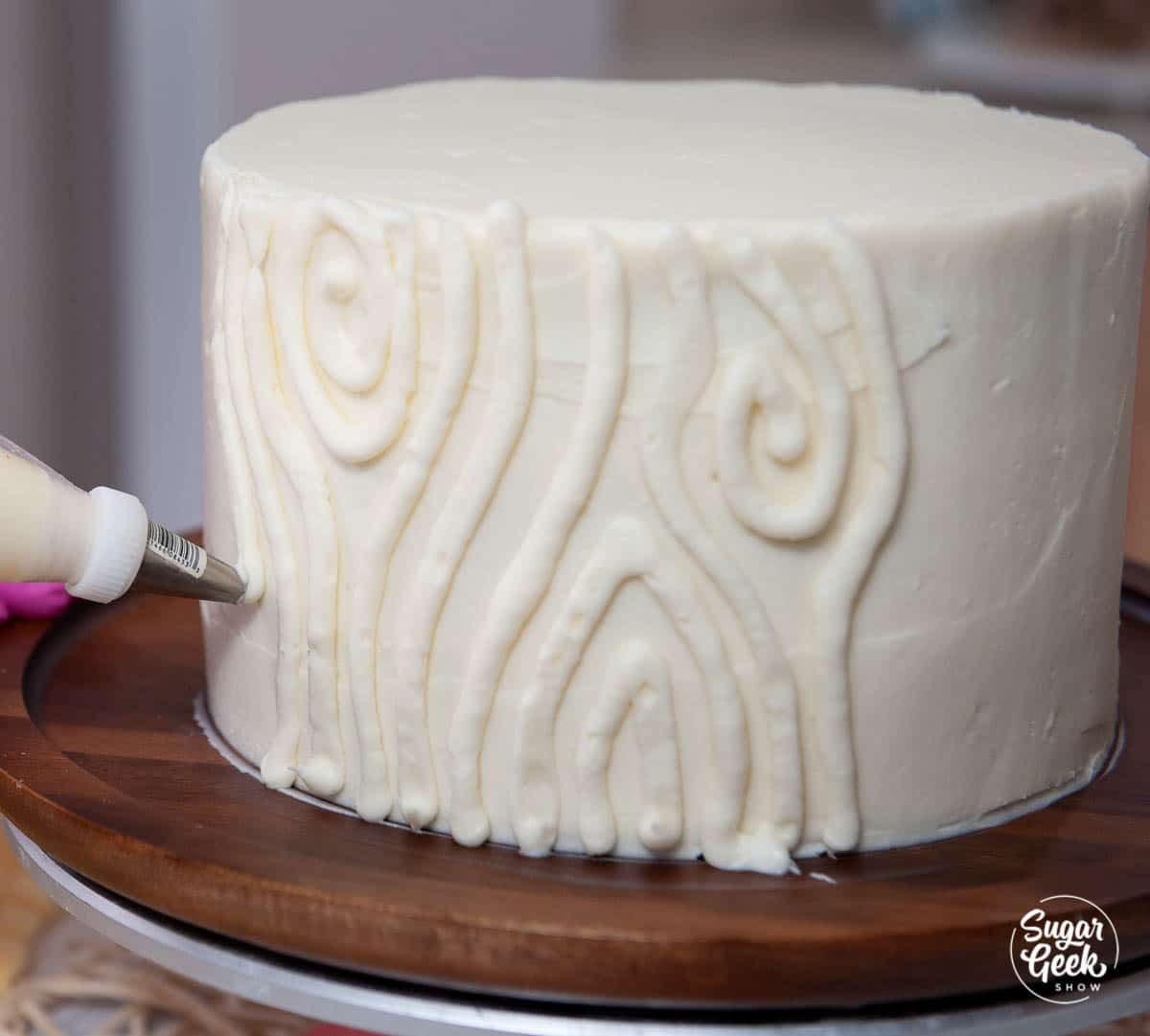 piping a wood grain texture onto the side of a cake