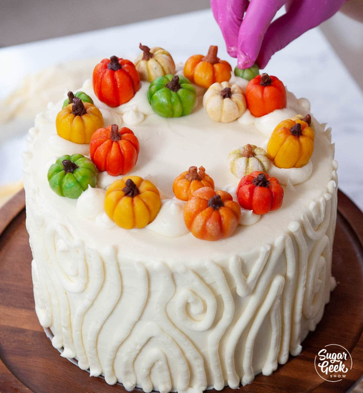 adding marzipan candy pumpkins to the top of the cake
