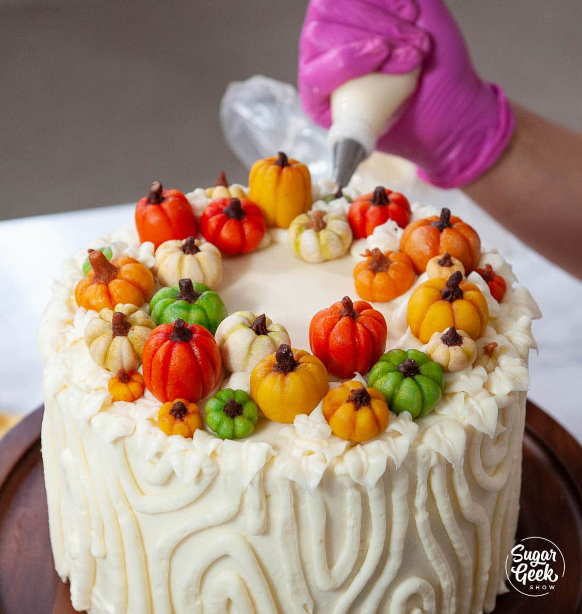 piping frosting leaves around the marzipan pumpkins