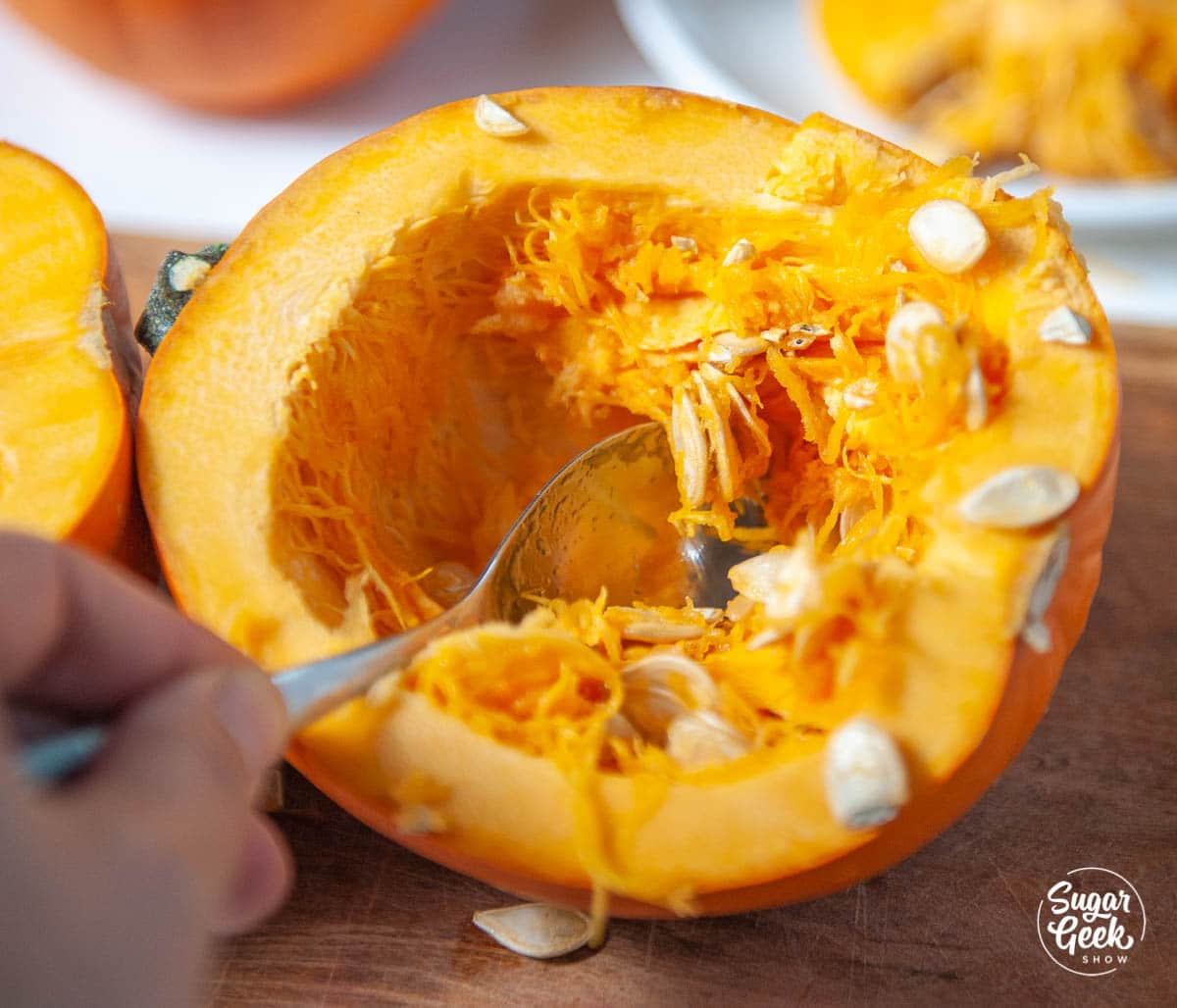 removing pumpkin seeds from a pumpkin with a spoon