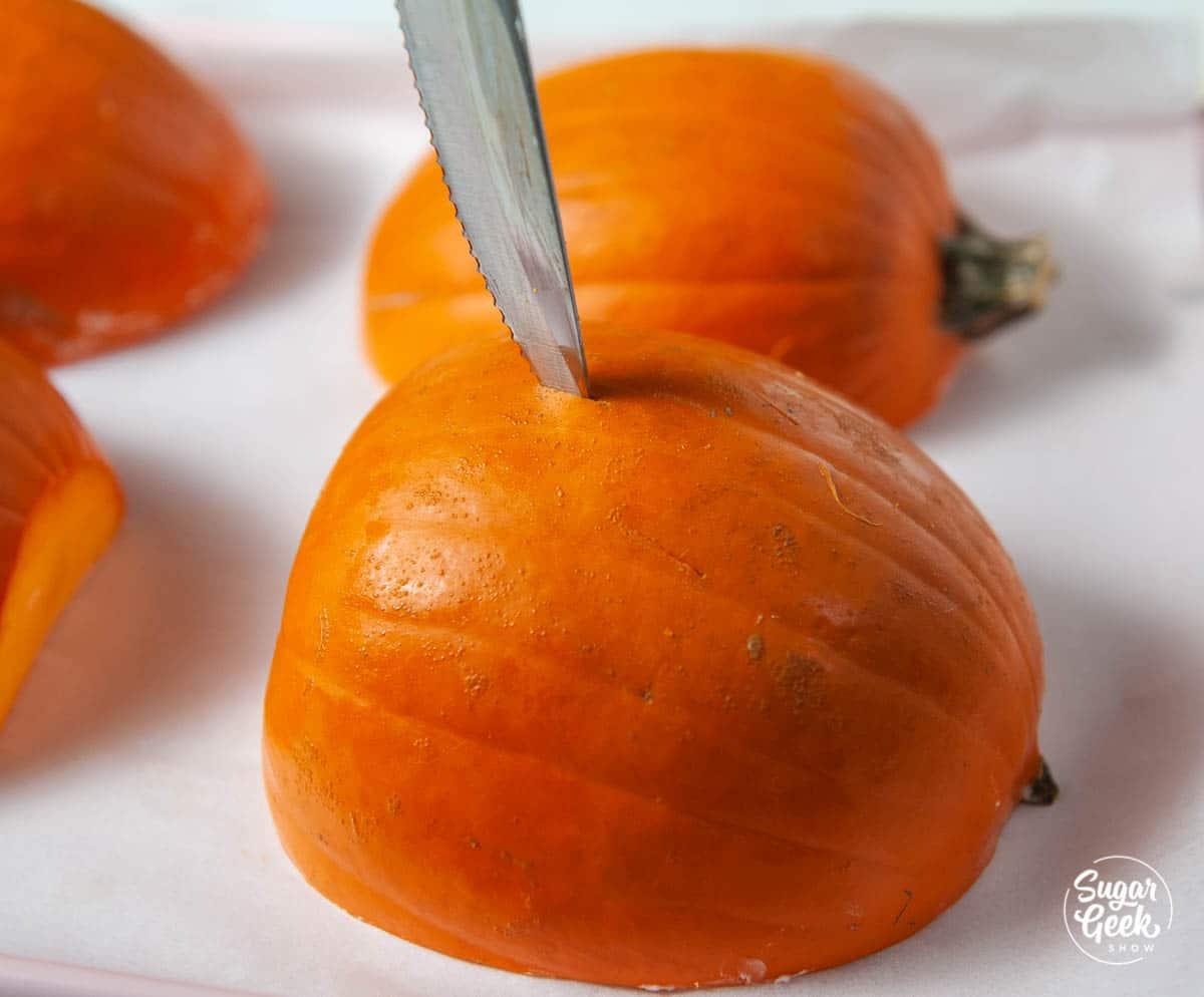 knife piercing the skin of a cut pumpkin