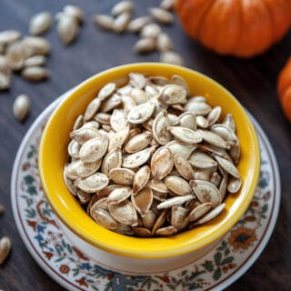 roasted pumpkin seeds in a yellow bowl
