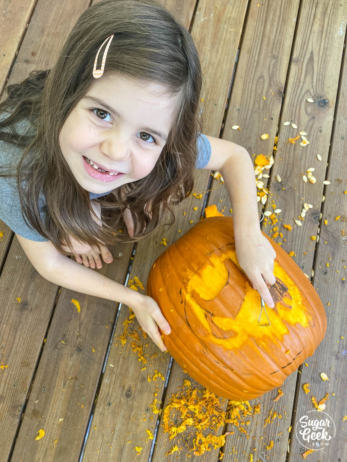 girl looking up from carved pumpkin