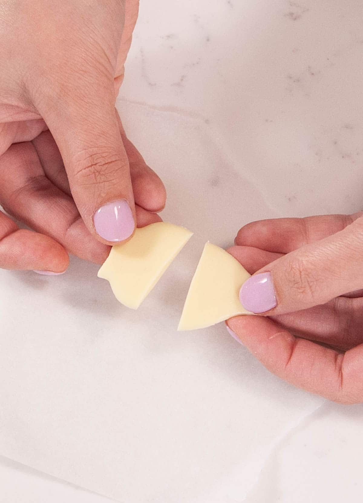 two hands holding two pieces of white chocolate