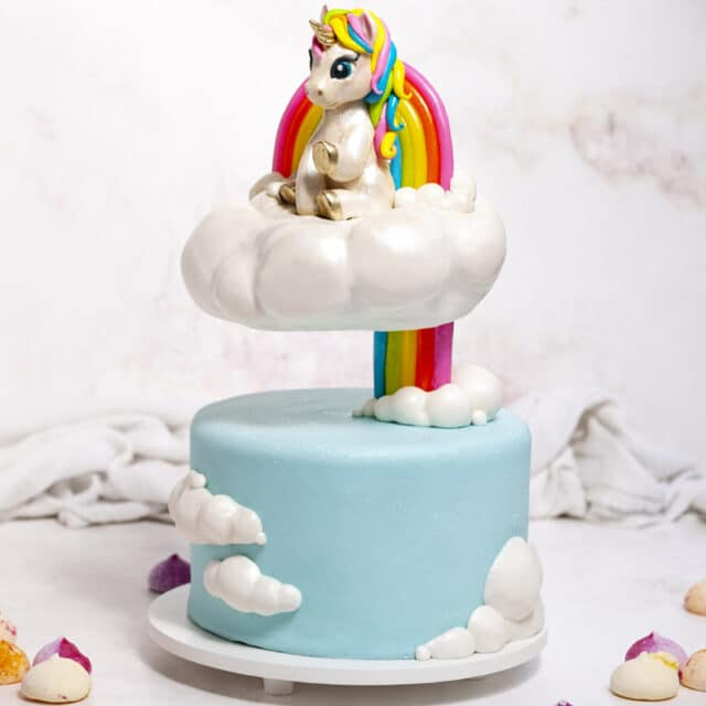 Cake with a floating cloud tier and rainbow with a unicorn cake topper sitting on top of it