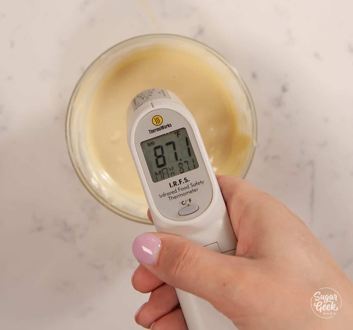 thermometer checking the temperature of a bowl of white chocolate shot from above