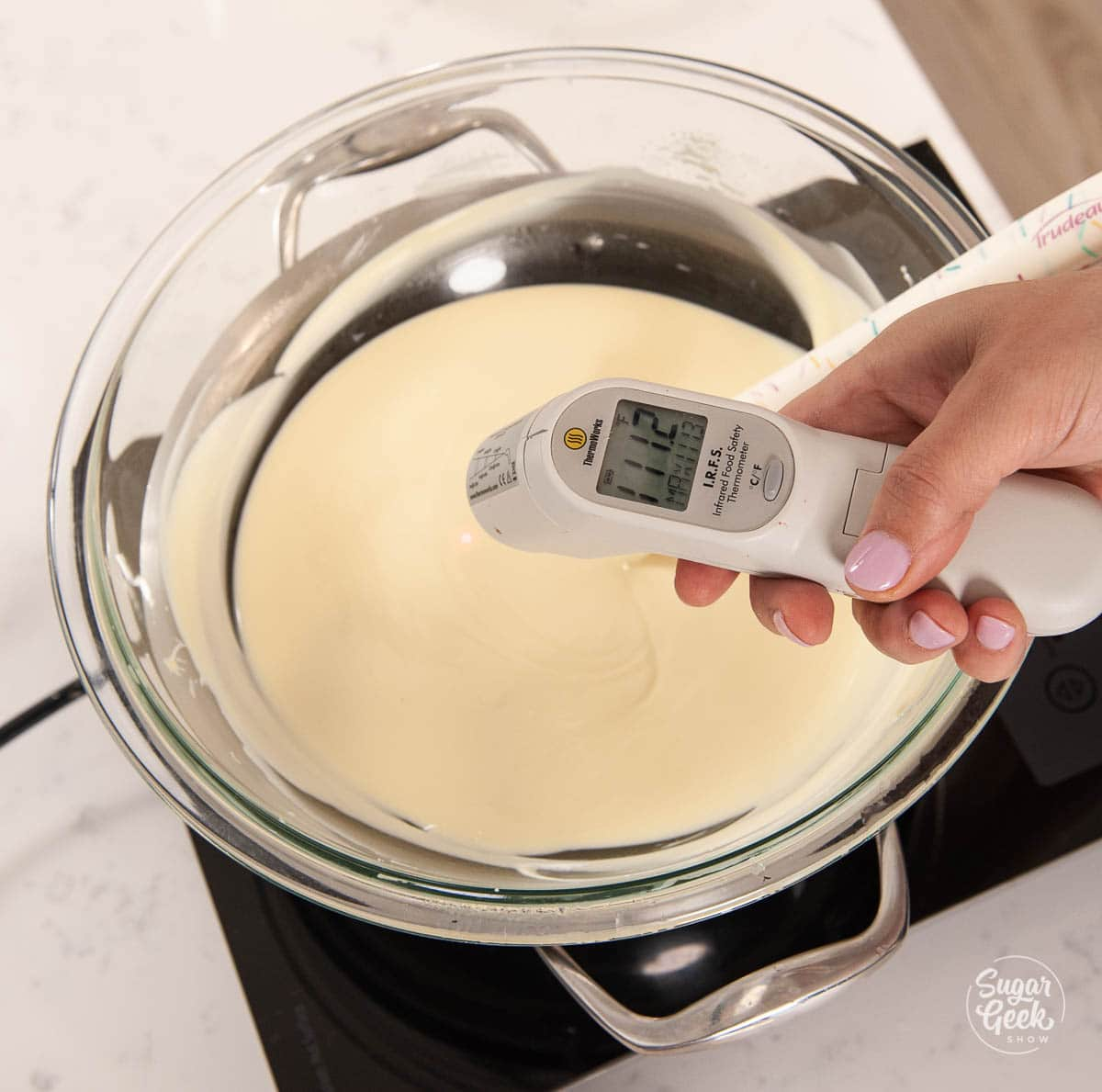 infrared thermometer held in hand over melted chocolate