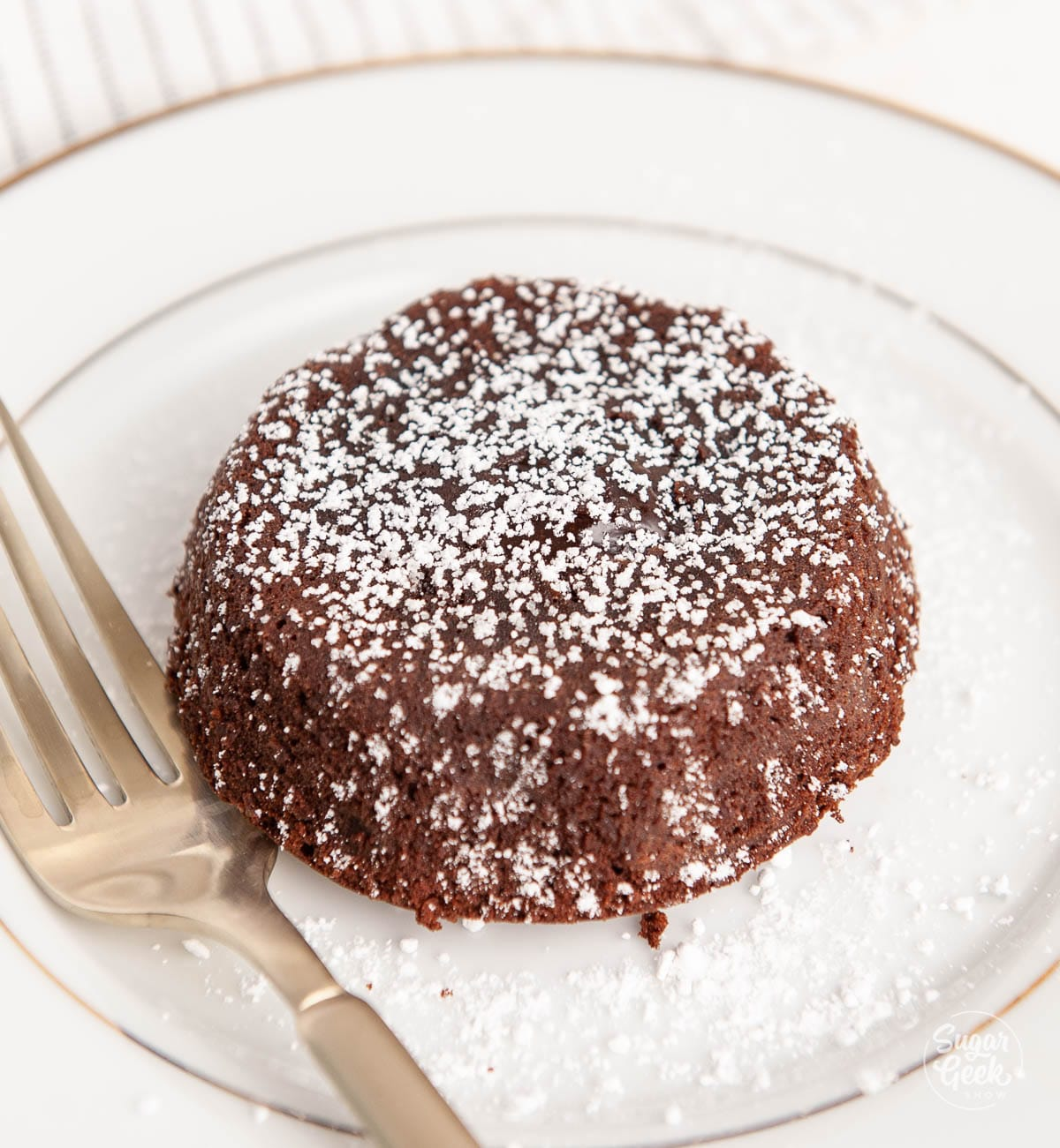 closeup of lava cake with powdered sugar on a white plate next to a gold fork