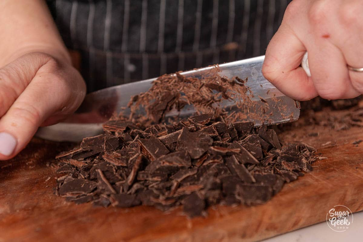 close up of knife and hands chopping chocolate