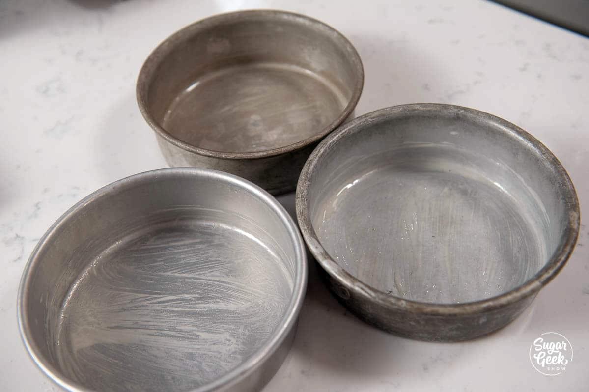 three cake pans prepared with cake goop