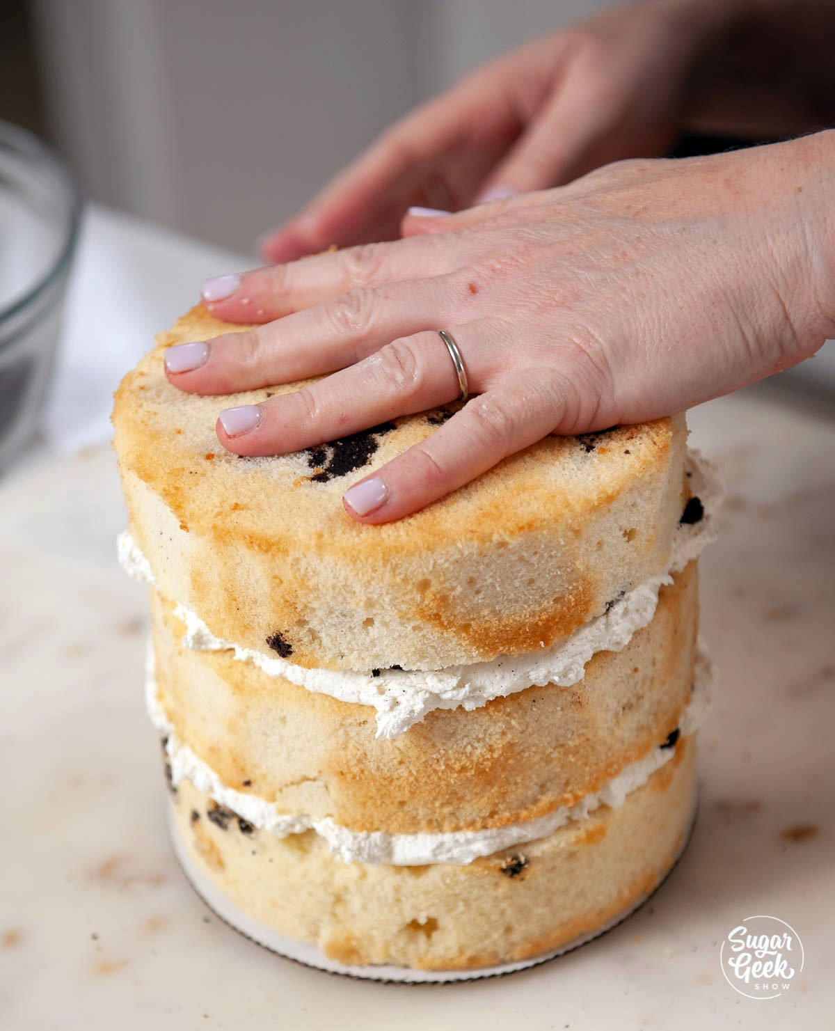 stacking layers of Oreo cake with frosting