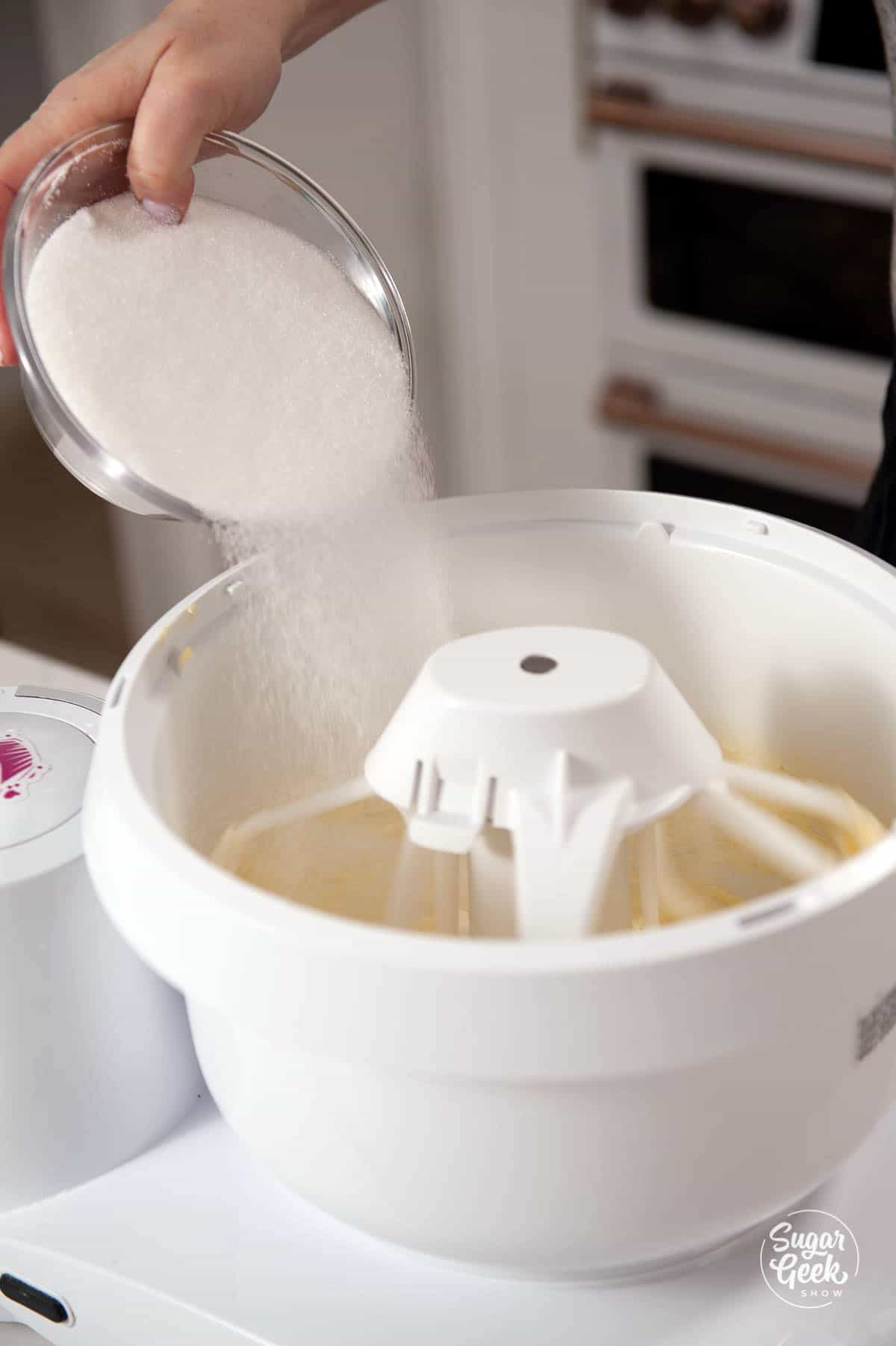 adding sugar to creaming butter in a mixer