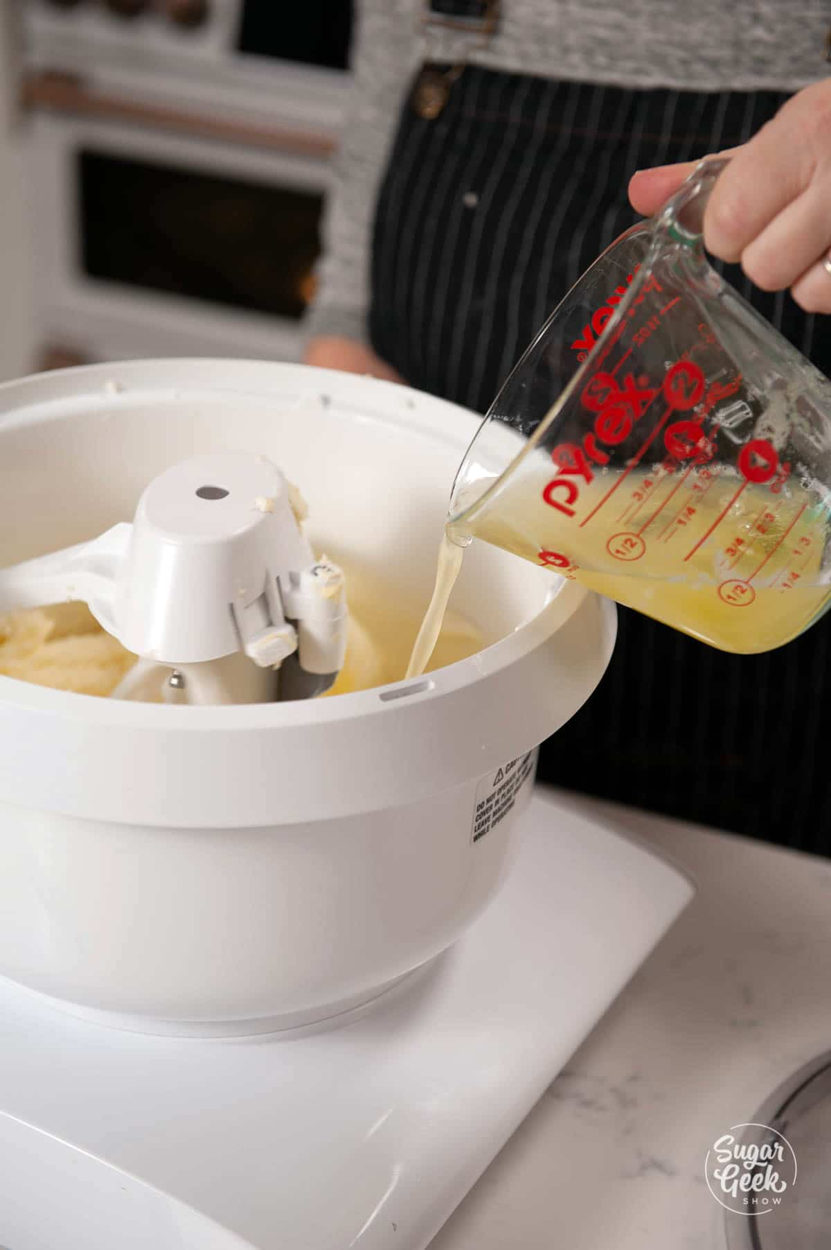 adding egg whites to whipping butter and sugar in a mixer