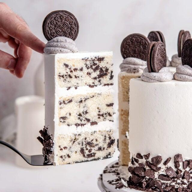 hand holding oreo cake slice next to oreo layer cake