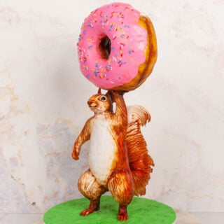 cake sculpted to look like a squirrel holding a giant donut