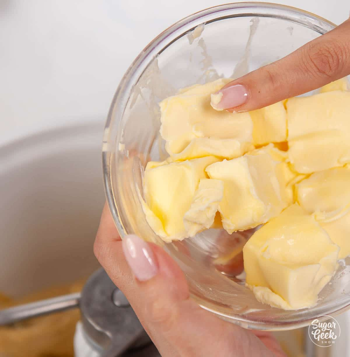closeup of finger pressing softened butter