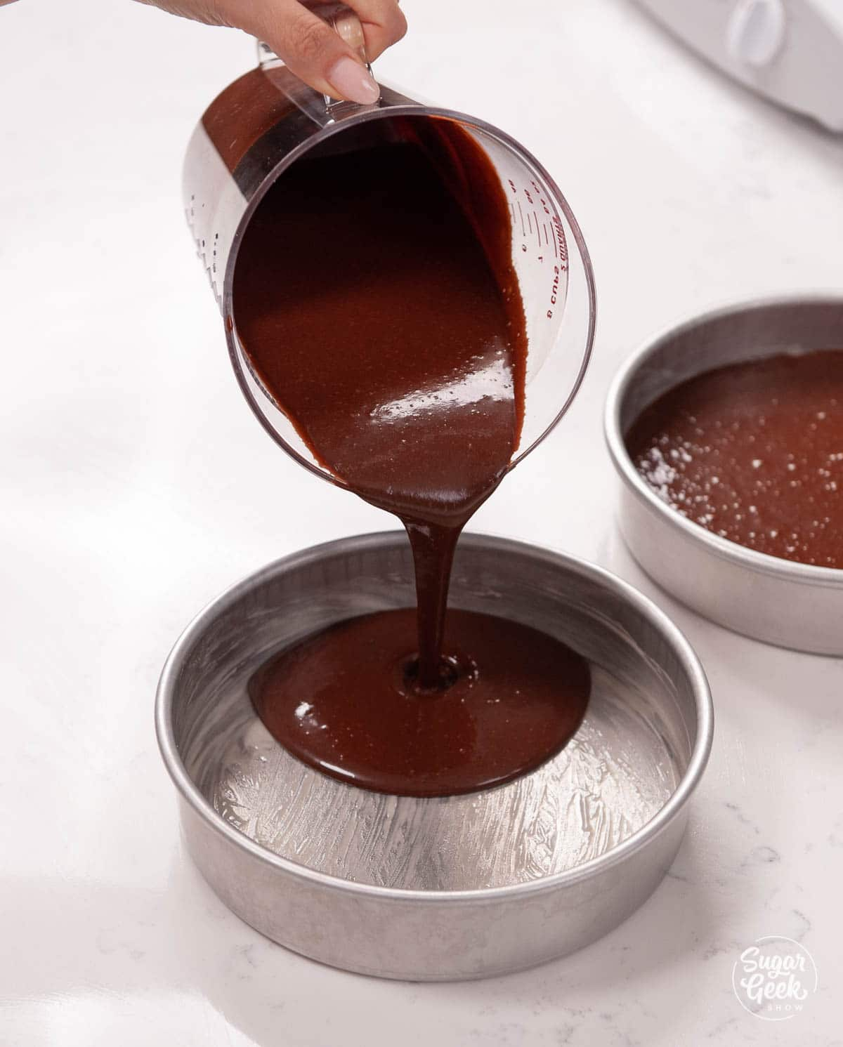 pouring chocolate batter into cake pans
