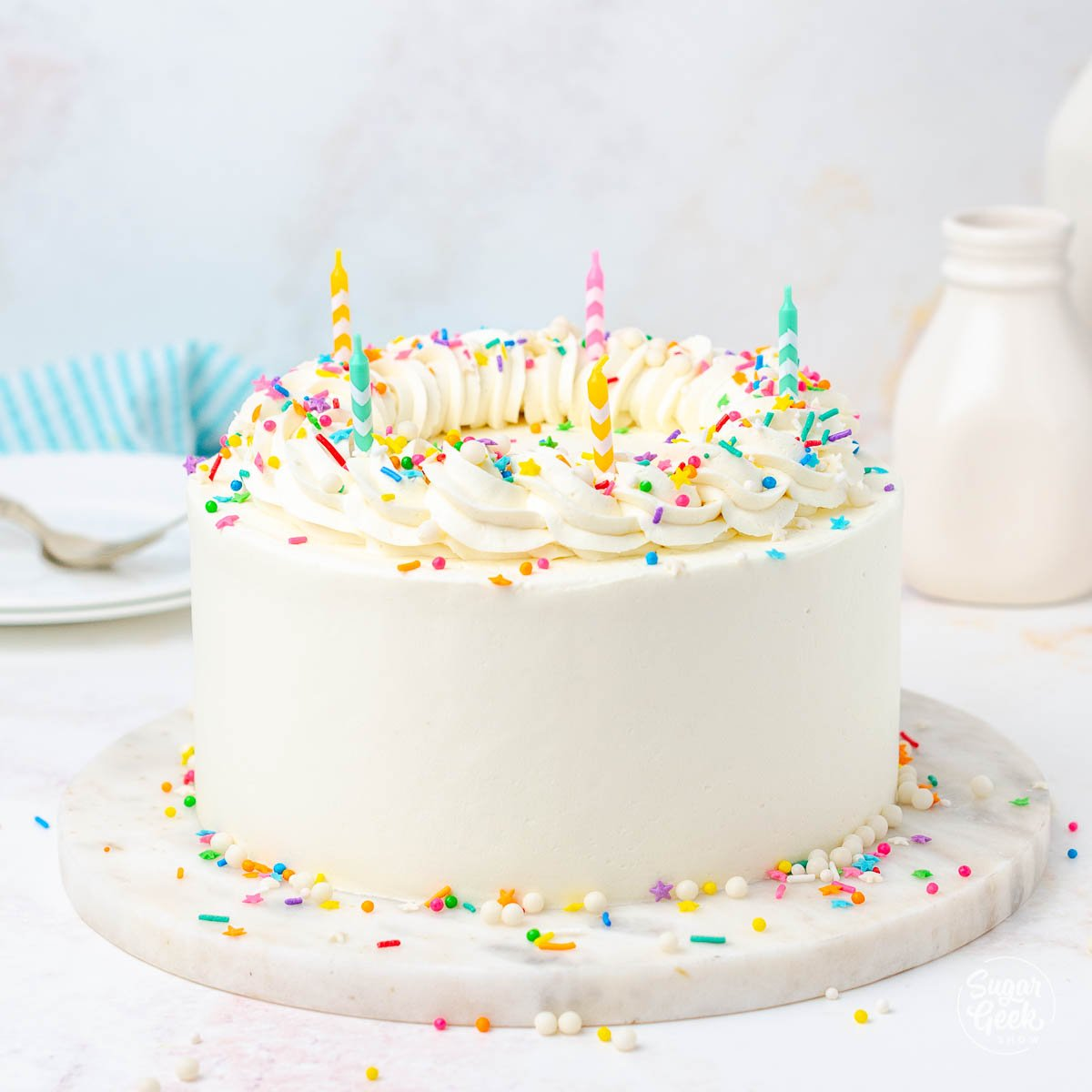 closeup of cake with white frosting and colorful sprinkles