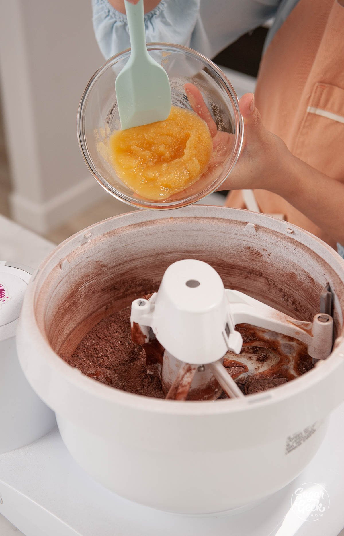 adding applesauce to chocolate cake batter in a mixing bowl