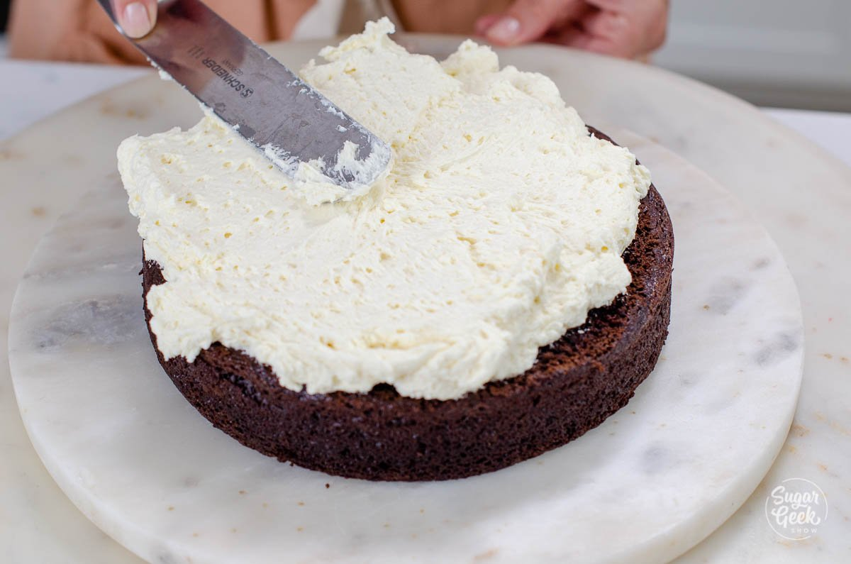 adding ermine frosting on top of the cake layer