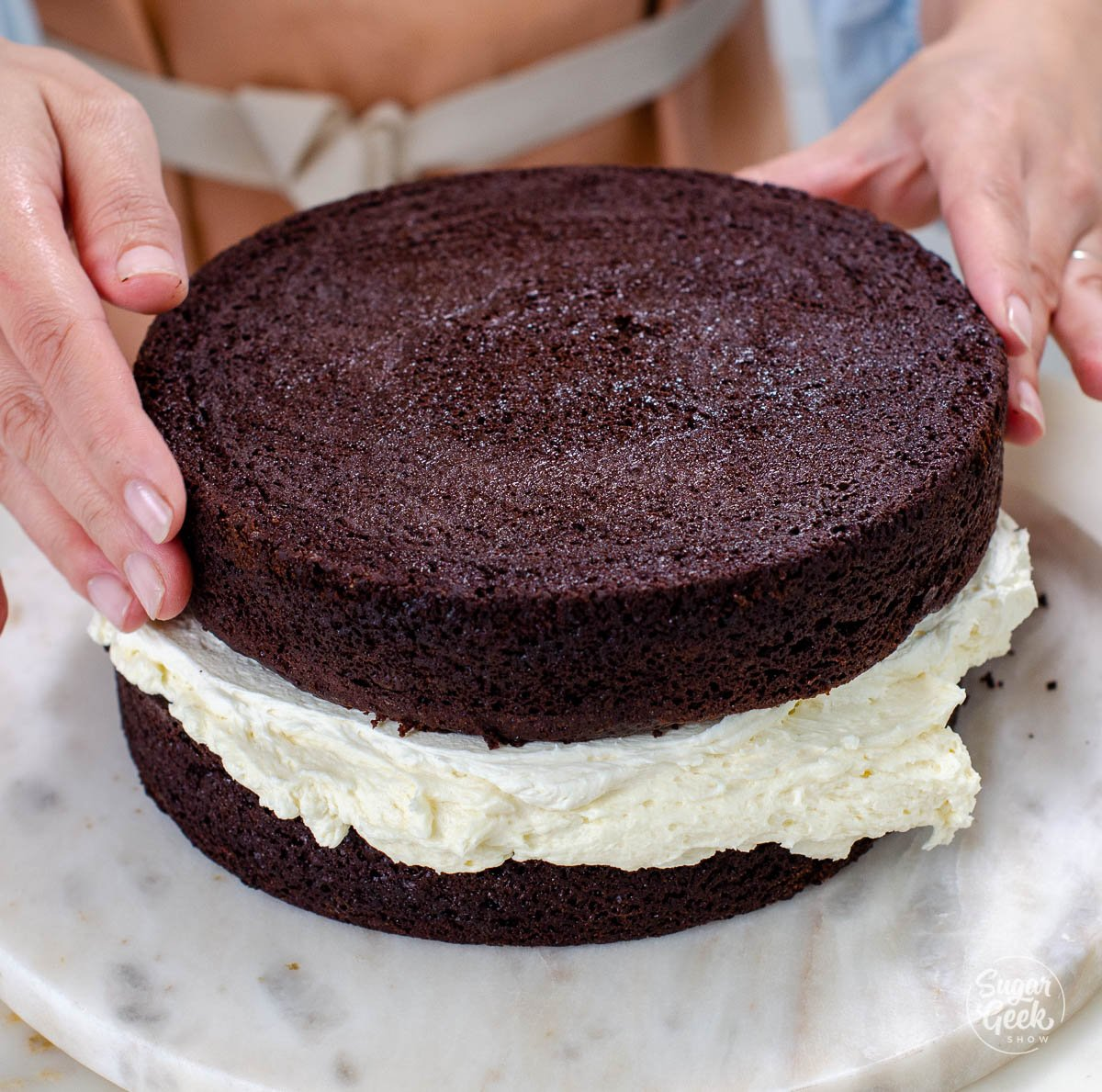 adding the second layer of cake to the frosting layer