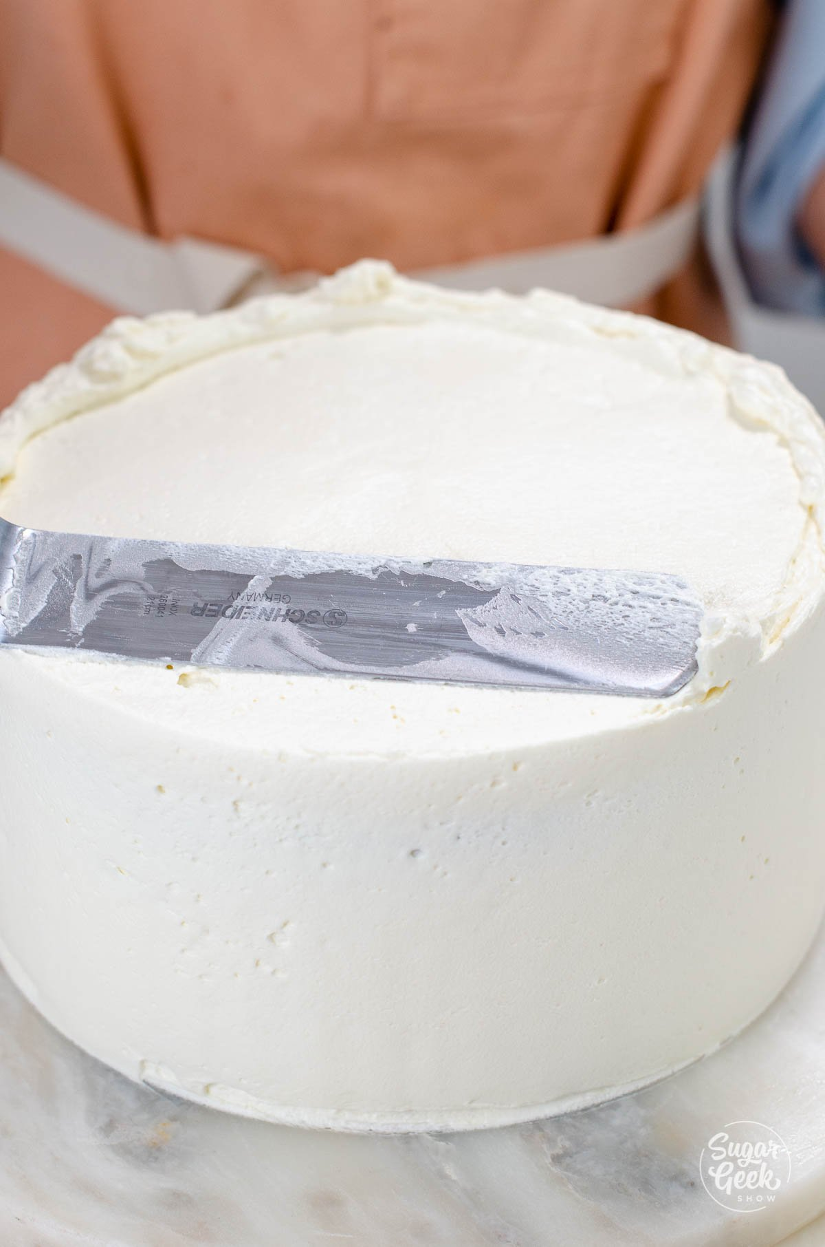 smoothing out the frosting with an offset spatula